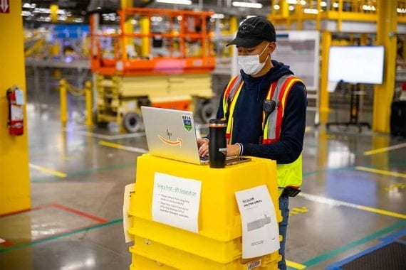 The pandemic has altered operations, including product returns, for many ecommerce merchants. Here a worker at an Amazon fulfillment center wears a mask.